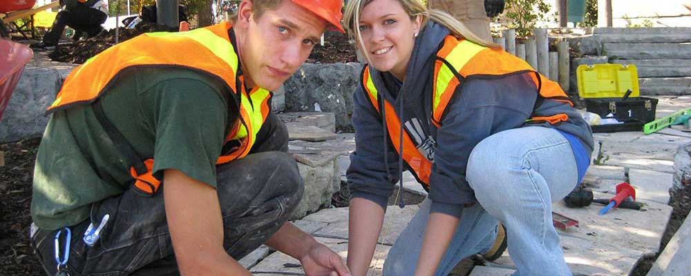 Two students work to set paving stones